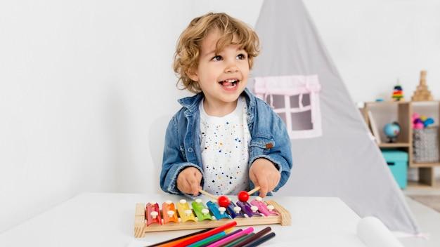 Vooraanzicht van het spelen van de jongen met xylofoon Gratis Foto