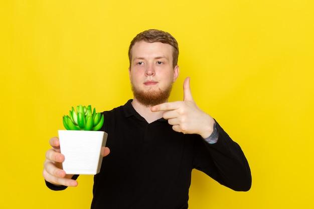 Vooraanzicht van jong mannetje in zwart overhemd dat weinig groene installatie houdt Gratis Foto