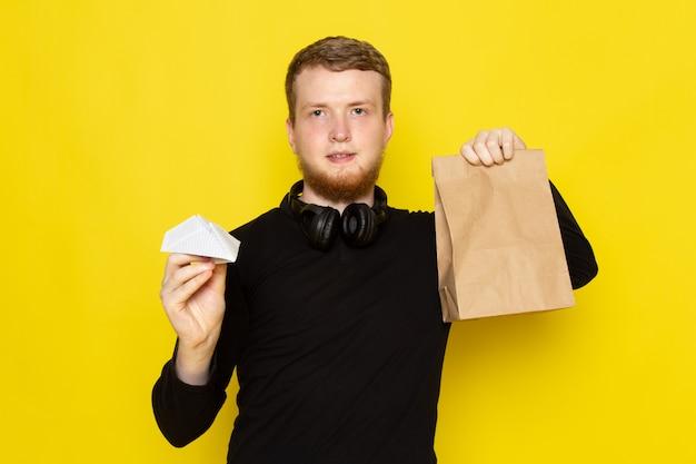 Vooraanzicht van jonge man in zwart shirt met papieren vliegtuigje en een goed pakket Gratis Foto
