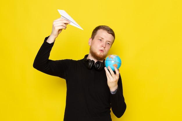 Vooraanzicht van jonge man in zwart shirt met papieren vliegtuigje en kleine globe vorm Gratis Foto