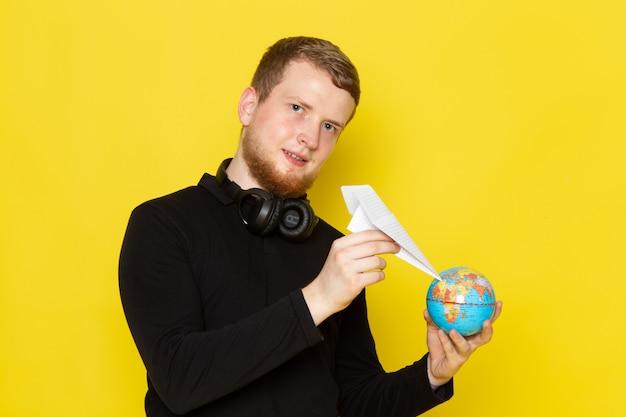 Vooraanzicht van jonge man in zwart shirt met papieren vliegtuigje en kleine wereldbol met glimlach Gratis Foto