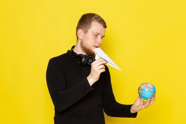 Vooraanzicht van jonge man in zwart shirt met papieren vliegtuigje en kleine wereldbol Gratis Foto