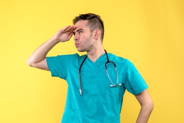 Vooraanzicht van jonge mannelijke arts die afstand op gele muur bekijkt Gratis Foto