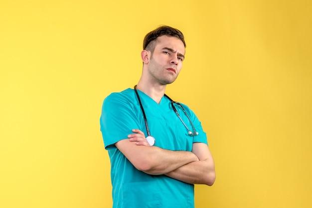 Vooraanzicht van jonge mannelijke arts die op gele muur denkt Gratis Foto