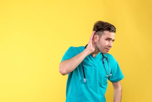Vooraanzicht van jonge mannelijke arts die op gele muur luistert Gratis Foto