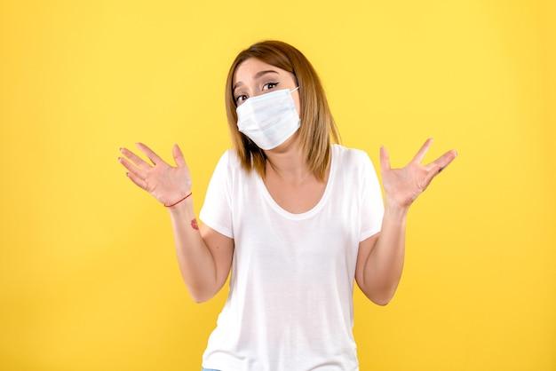 Vooraanzicht van jonge vrouw in steriel masker op lichtgele muur Gratis Foto