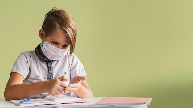 Vooraanzicht van kind met medisch masker desinfecterende handen in de klas met kopie ruimte Gratis Foto