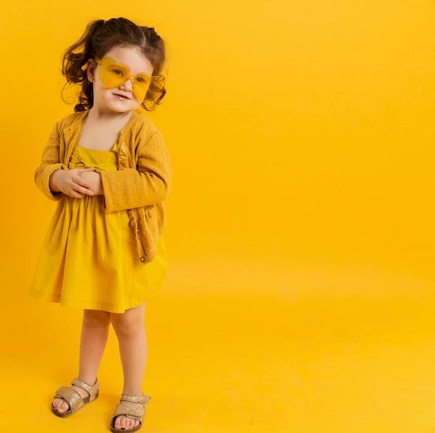 Vooraanzicht van kind poseren tijdens het dragen van een zonnebril Gratis Foto