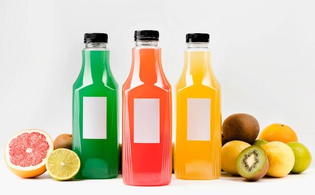 Vooraanzicht van kleurrijke sapflessen met doppen en fruit Gratis Foto