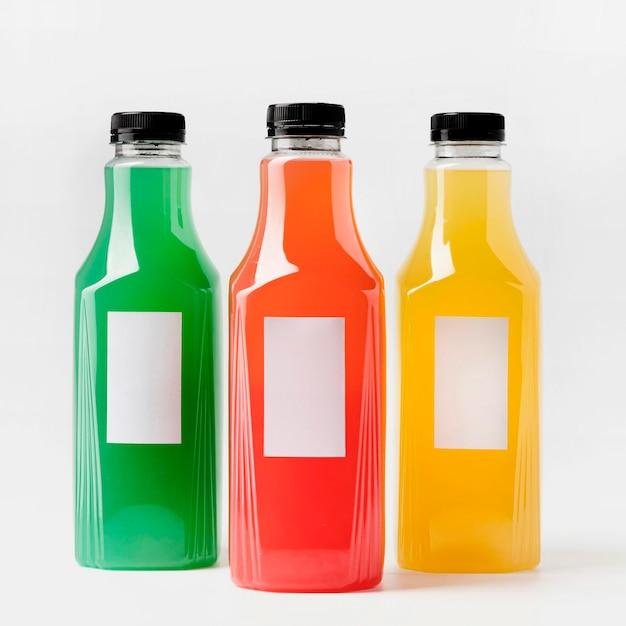 Vooraanzicht van kleurrijke sapflessen met doppen Gratis Foto