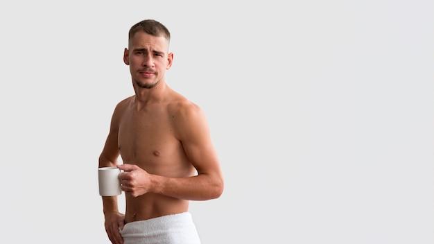 Vooraanzicht van knap in de ochtend met koffie en exemplaarruimte Gratis Foto