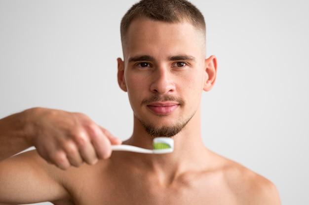 Vooraanzicht van knappe man met tandenborstel met tandpasta erop Gratis Foto