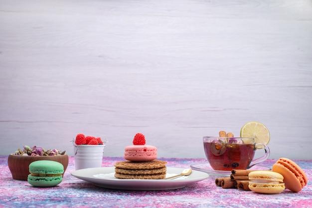 Vooraanzicht van koekjes en macarons met thee en kaneel op het lichte bureau Gratis Foto