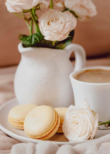 Vooraanzicht van koffie in de ochtend met rozen en macarons Gratis Foto