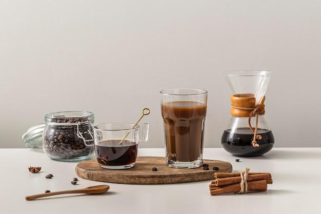 Vooraanzicht van koffie in verschillende containers en pijpjes kaneel Premium Foto