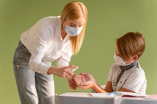 Vooraanzicht van leraar met medisch masker desinfecterende kind handen in de klas Gratis Foto