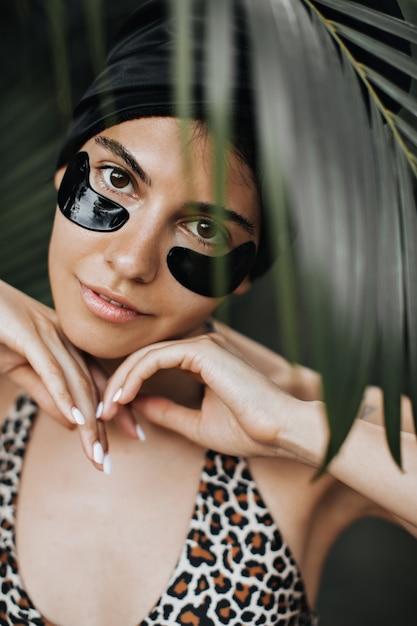 Vooraanzicht van leuke vrouw met ooglapjes onder palmboom. mooie vrouwelijke model poseren op tropische achtergrond. Gratis Foto