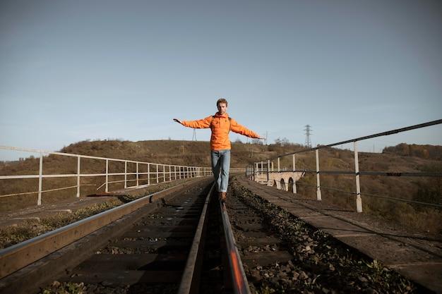 Vooraanzicht van man balanceren op spoorweg tijdens een road trip Premium Foto