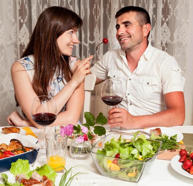 Vooraanzicht van man en vrouw aan tafel met wijn en eten Gratis Foto