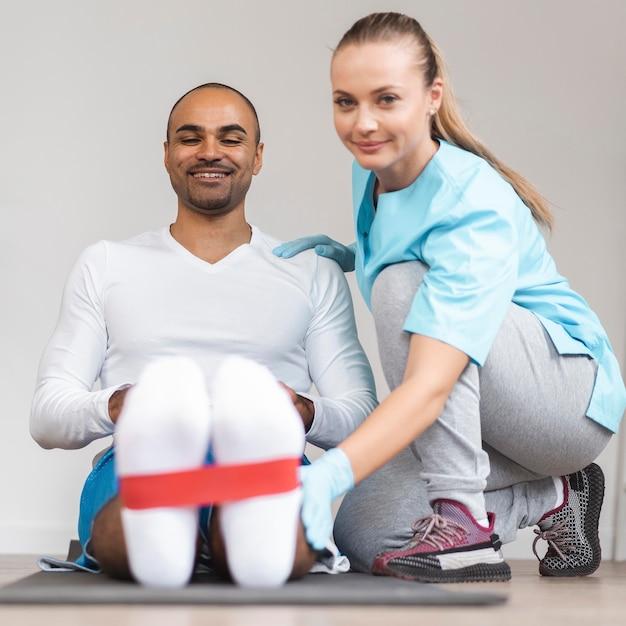 Vooraanzicht van man en vrouwelijke fysiotherapeut die oefeningen doen Gratis Foto