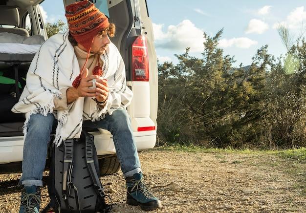 Vooraanzicht van man zittend op de kofferbak van de auto tijdens een roadtrip Gratis Foto