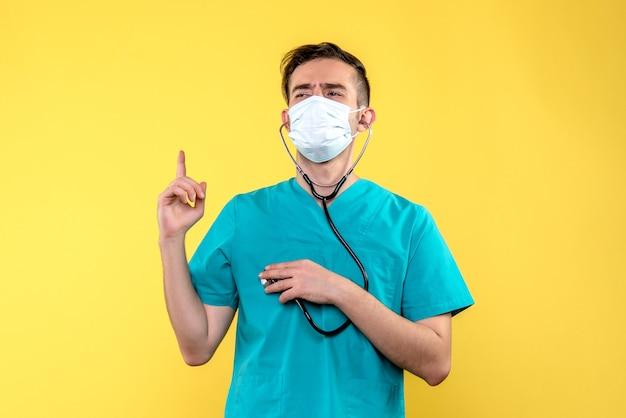 Vooraanzicht van mannelijke arts met stethoscoop en masker op gele muur Gratis Foto