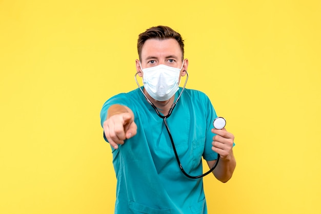 Vooraanzicht van mannelijke arts met tonometer en masker op gele muur Gratis Foto