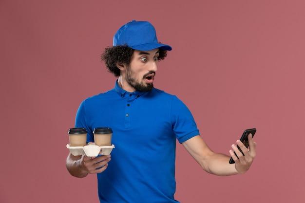 Vooraanzicht van mannelijke koerier in blauw uniform en pet met koffiekopjes voor levering en werktelefoon op zijn handen op de roze muur Gratis Foto