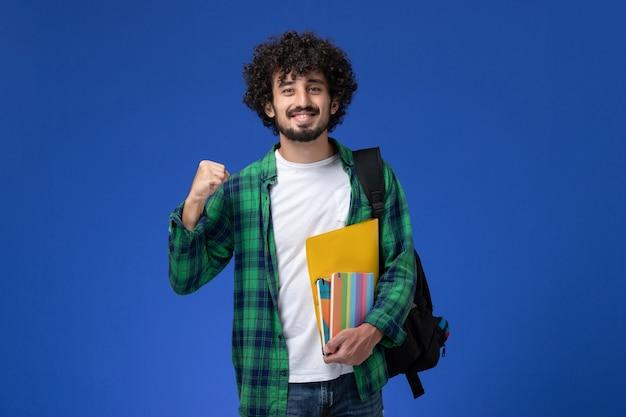 Vooraanzicht van mannelijke student die zwarte rugzak draagt die voorbeeldenboeken en dossiers op de blauwe muur houdt Gratis Foto