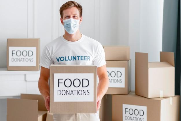 Vooraanzicht van mannelijke vrijwilliger met voedseldonatiebox Premium Foto