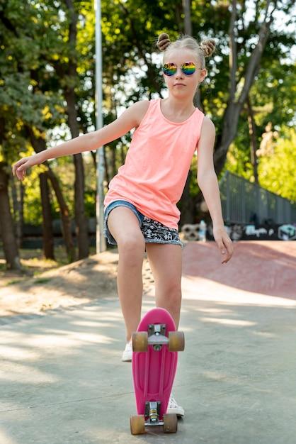 Vooraanzicht van meisje op roze skateboard Gratis Foto