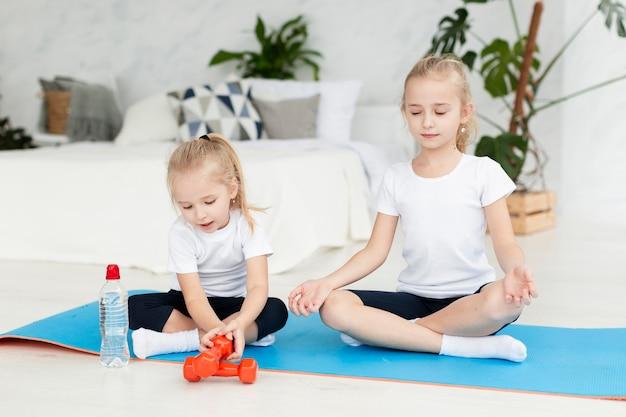 Vooraanzicht van meisjes die thuis op yogamat uitoefenen Gratis Foto