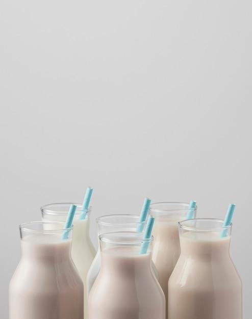 Vooraanzicht van melkflesbovenkanten met rietjes en exemplaarruimte Gratis Foto