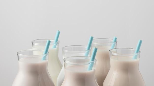 Vooraanzicht van melkflesbovenkanten met rietjes Gratis Foto