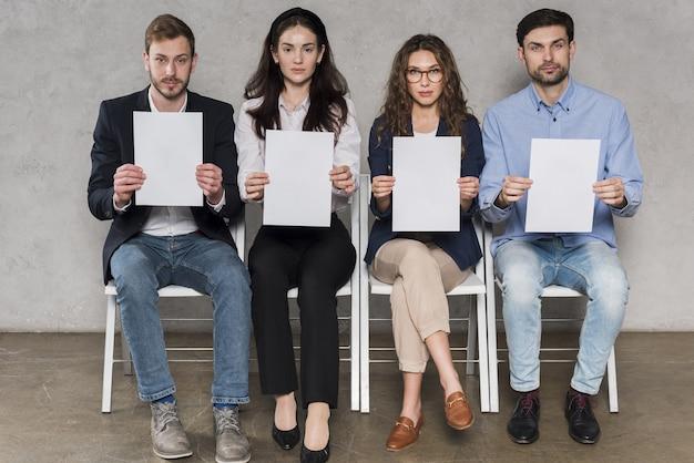 Vooraanzicht van mensen die op hun sollicitatiegesprekken wachten die lege documenten houden Gratis Foto