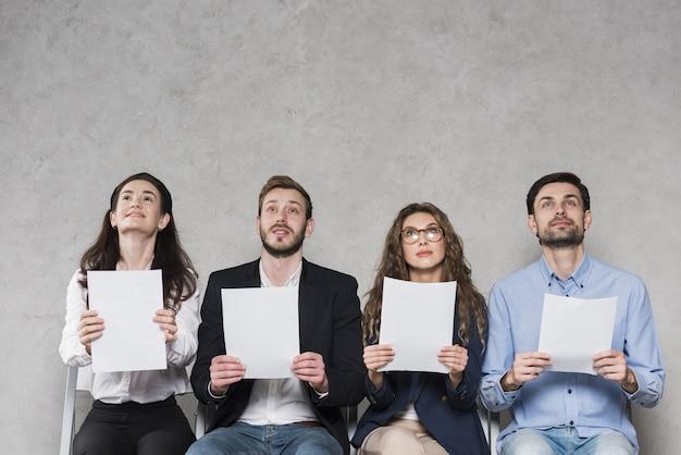 Vooraanzicht van mensen die op hun sollicitatiegesprekken wachten die lege documenten met exemplaarruimte houden Premium Foto