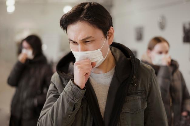 Vooraanzicht van mensen met medische maskers hoesten Gratis Foto
