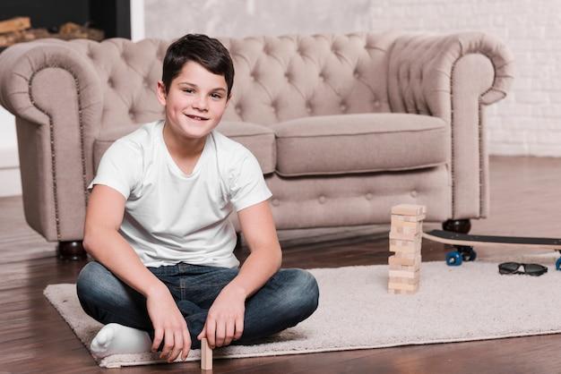 Vooraanzicht van moderne jongenszitting op vloer Gratis Foto
