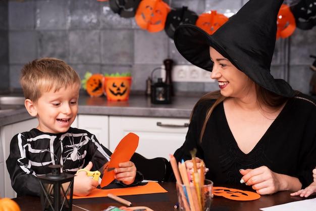 Vooraanzicht van moeder en zoon in de keuken Gratis Foto