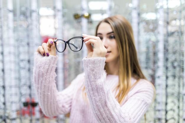 Vooraanzicht van mooi meisje in witte trui probeer glazen in de winkel op Gratis Foto
