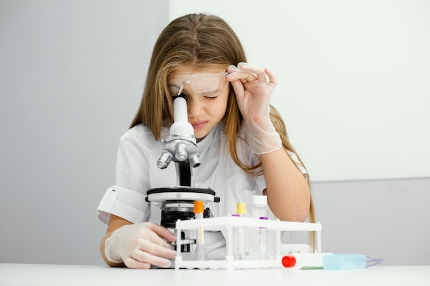 Vooraanzicht van nieuwsgierige jonge meisjeswetenschapper die microscoop met behulp van Gratis Foto
