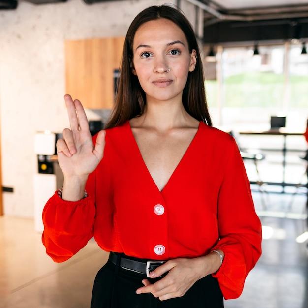 Vooraanzicht van onderneemster die gebarentaal gebruikt Gratis Foto