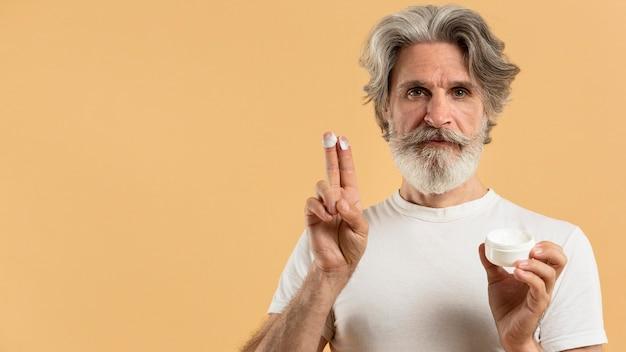 Vooraanzicht van oudere bebaarde man met vochtinbrengende crème en kopie ruimte Gratis Foto