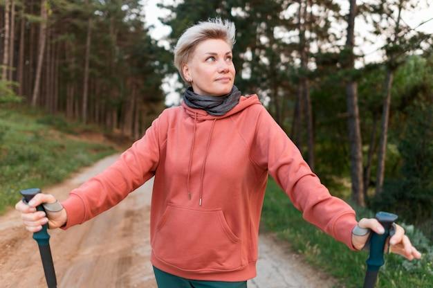 Vooraanzicht van oudere toeristenvrouw in het bos met wandelstokken Gratis Foto