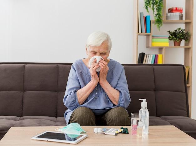 Vooraanzicht van oudere vrouw die haar neus in servet blaast Gratis Foto