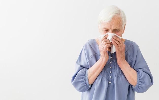 Vooraanzicht van oudere vrouw die haar neus met exemplaarruimte blaast Gratis Foto