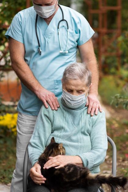 Vooraanzicht van oudere vrouw met medisch masker en kat verzorgd door een verpleger Gratis Foto