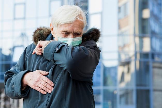 Vooraanzicht van oudere vrouw met medische masker hoesten in haar elleboog Gratis Foto