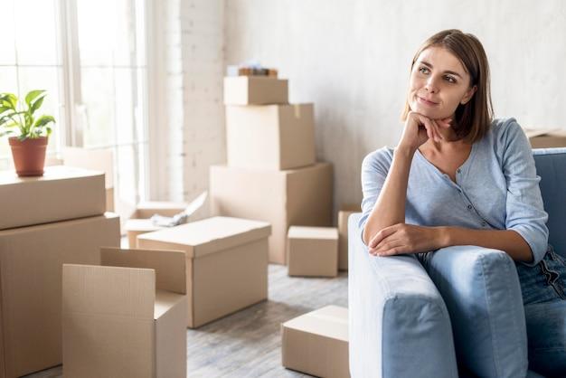 Vooraanzicht van peinzende vrouw op de bank klaar om te verhuizen Gratis Foto