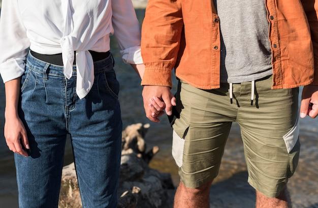 Vooraanzicht van romantisch paar hand in hand terwijl op het strand Gratis Foto
